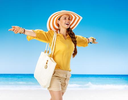 Été parfait. heureuse femme en bonne santé en short et chemisier jaune avec sac de plage blanc sur le bord de la mer se réjouir Banque d'images