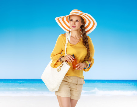 Perfect summer. pensive young woman in shorts and yellow blouse with white beach bag on the seashore with sun cream looking into the distance Foto de archivo - 93407990