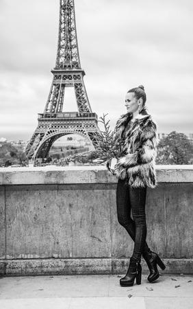 La saison des fêtes à Paris. Portrait de pleine longueur d'une femme branchée avec un sapin de Noël en manteau de fourrure contre la tour Eiffel à Paris, France Banque d'images - 93407995