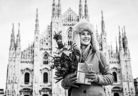 밀라노, 이탈리아에 재미있는 크리스마스 여행. 크리스마스 트리 및 거리를 찾고 선물 밀라노, 이태리에서 두오모 앞의 행복 한 현대 여행자 여자 스톡 콘텐츠