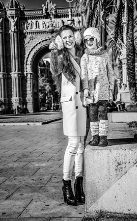 in Barcelona for a perfect winter. Full length portrait of smiling modern mother and child near Arc de Triomf in Barcelona, Spain pointing on something Stok Fotoğraf