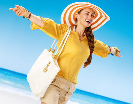 Perfect summer. happy healthy woman in shorts and yellow blouse with white beach bag on the seacoast rejoicing