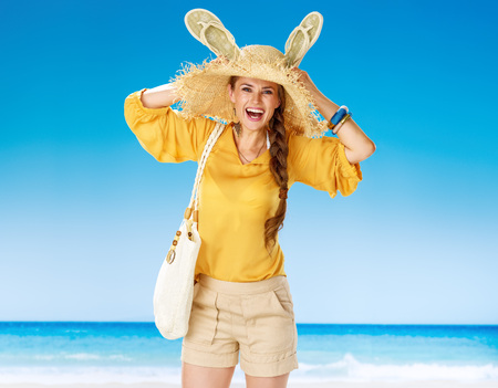 Perfect summer. happy healthy woman in shorts and yellow blouse with white beach bag on the seacoast showing ears made from beach slipper