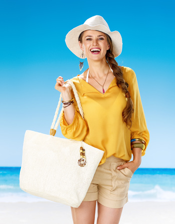Perfect summer. Portrait of happy woman in shorts and yellow blouse with white beach bag on the beach Stock Photo
