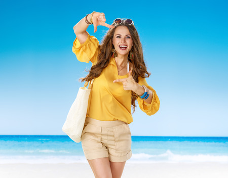 Perfect summer. smiling woman in shorts and yellow blouse with white beach bag on the seacoast with hands framing Stok Fotoğraf