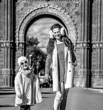 in Barcelona for a perfect winter. Full length portrait of happy trendy mother and child standing near Arc de Triomf in Barcelona, Spain