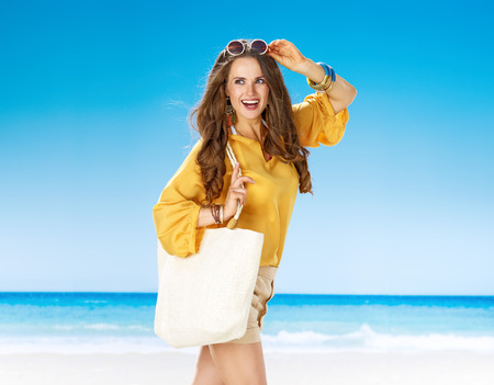 Perfect summer. happy woman in shorts and yellow blouse with white beach bag on the seacoast looking aside