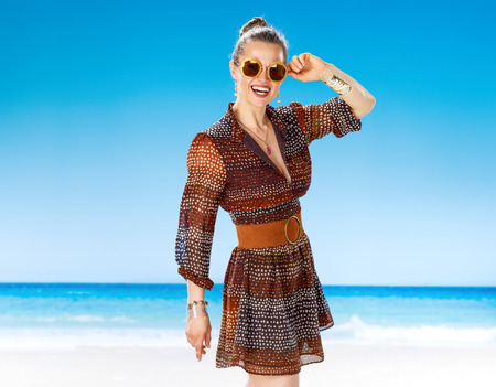 Perfect summer. smiling young woman in summer dress on the beach in sunglasses