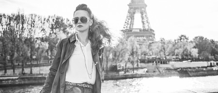 Autumn getaways in Paris. Portrait of young elegant woman in sunglasses on embankment in Paris, France looking into the distance