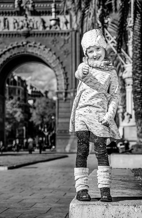 in Barcelona for a perfect winter. Full length portrait of happy modern child in Barcelona, Spain showing thumbs up Stok Fotoğraf