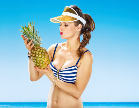 Perfect summer. smiling healthy woman in swimwear on the beach holding pineapple