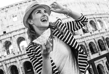 Roman Holiday. happy trendy tourist woman in Rome, Italy with pizza slice looking into the distance Stock Photo