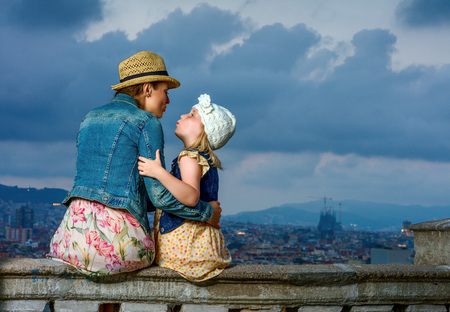 Perfect evening with stunning view. Seen from behind young mother and child travellers against city panorama of Barcelona, Spain kissing Banco de Imagens