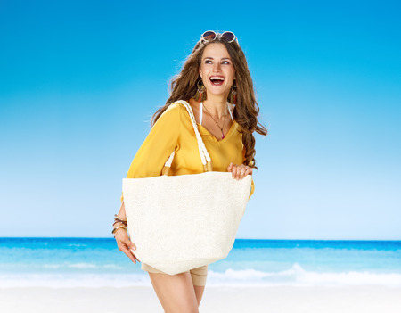 Perfect summer. smiling active woman in shorts and yellow blouse with white beach bag on the seashore looking into the distance 版權商用圖片
