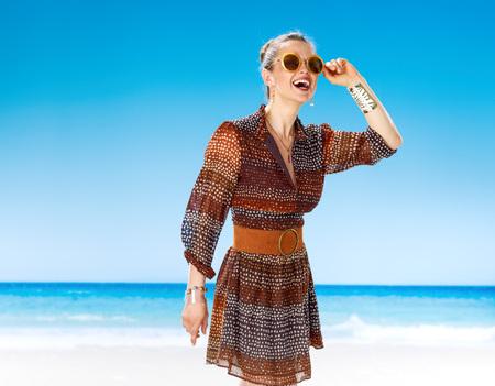 Été parfait. femme en bonne santé souriante en été robe sur la plage regardant au loin dans les lunettes de soleil Banque d'images