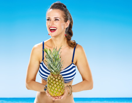 Perfect summer. happy woman in beachwear on the seashore with pineapple looking into the distance 版權商用圖片