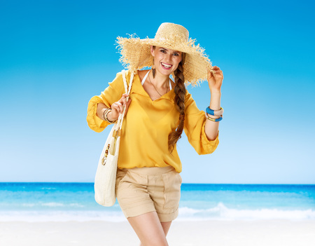 Perfect summer. Portrait of happy woman in shorts and yellow blouse with white beach bag on the seashore