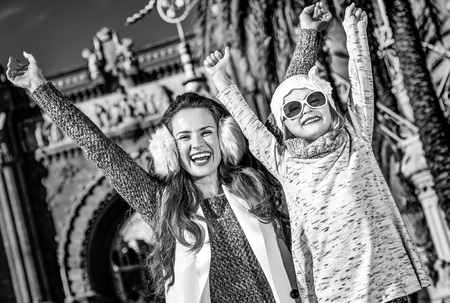 in Barcelona for a perfect winter. happy trendy mother and child near Arc de Triomf in Barcelona, Spain rejoicing