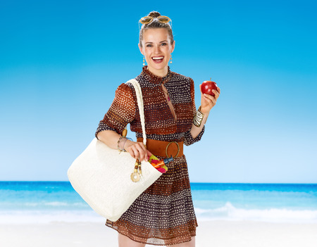 Perfect summer. happy healthy woman in summer dress with white beach bag on the beach eating an apple