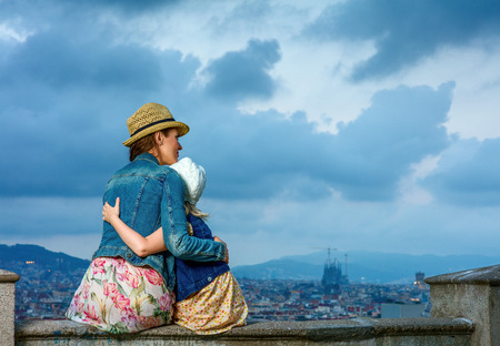 Perfect evening with stunning view. Seen from behind stylish mother and daughter travellers in the front of city panorama of Barcelona, Spain playing