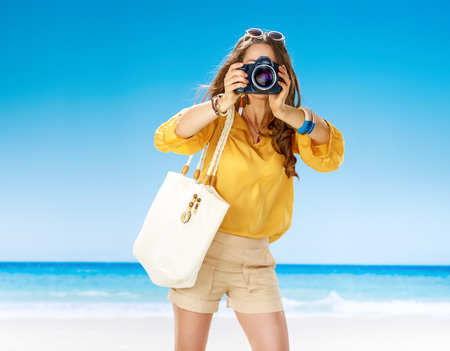 Perfect summer. woman in shorts and yellow blouse with white beach bag on the beach with digital camera taking photo Zdjęcie Seryjne