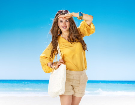 Perfect summer. smiling healthy woman in shorts and yellow blouse with white beach bag on the beach looking into the distance