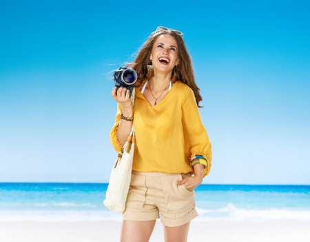 Perfect summer. smiling young woman in shorts and yellow blouse with white beach bag on the beach with digital SLR camera looking at copy space