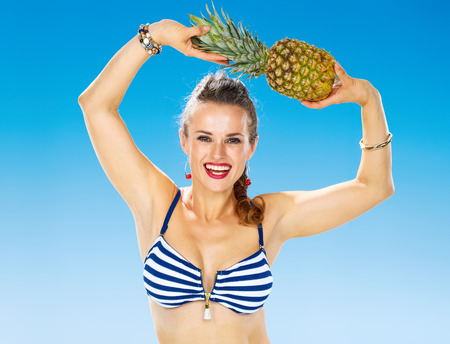Perfect summer. Portrait of cheerful young woman in swimsuit on the seashore with pineapple Stock Photo