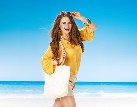 Perfect summer. Portrait of smiling woman in shorts and yellow blouse with white beach bag on the seashore