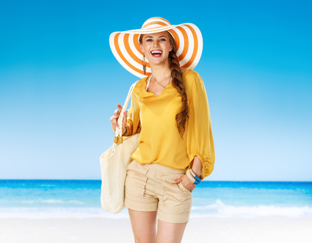 Perfect summer. Portrait of smiling active woman in shorts and yellow blouse with white beach bag on the beach Stok Fotoğraf