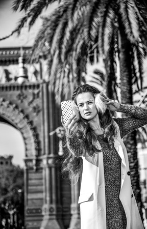 in Barcelona for a perfect winter. Portrait of young woman in earmuffs near Arc de Triomf in Barcelona, Spain with smartphone taking selfie Stok Fotoğraf