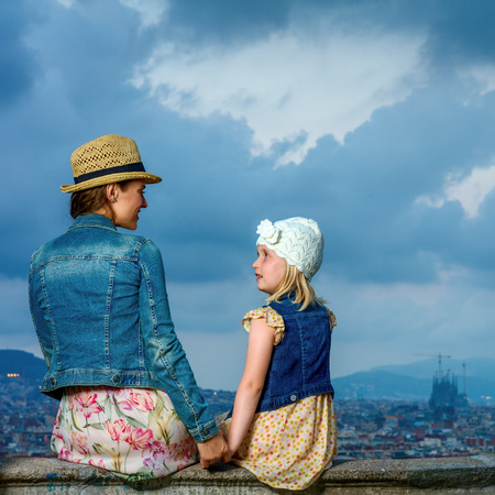 Perfect evening with stunning view. Seen from behind trendy mother and child tourists against city panorama of Barcelona, Spain looking at each other