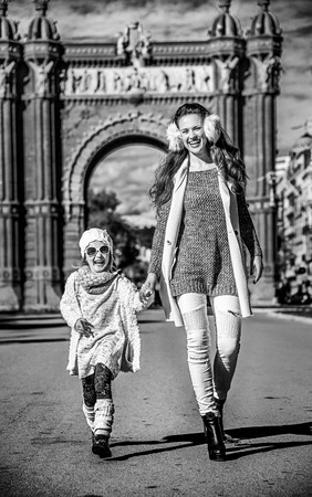 in Barcelona for a perfect winter. Full length portrait of smiling trendy mother and daughter near Arc de Triomf in Barcelona, Spain walking