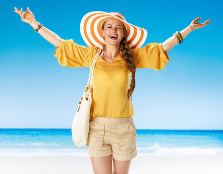 Perfect summer. happy young woman in shorts and yellow blouse with white beach bag on the seacoast rejoicing