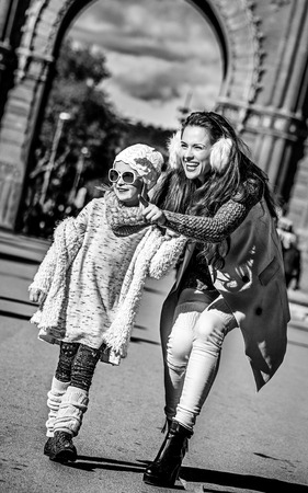 in Barcelona for a perfect winter. Full length portrait of happy trendy mother pointing on something to child near Arc de Triomf in Barcelona, Spain
