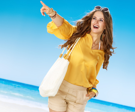 Perfect summer. smiling woman in shorts and yellow blouse with white beach bag on the beach pointing at something Stok Fotoğraf