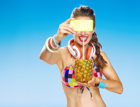 Perfect summer. happy healthy woman with headphones and wearing colorful swimsuit on the beach with refresh summer cocktail in pineapple with digital camera taking photo
