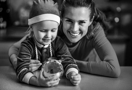 웃는 엄마와 아기가 크리스마스 공을 들고 초상화 스톡 콘텐츠
