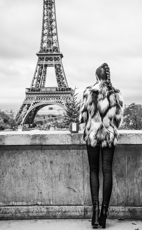 The Party Season in Paris. Seen from behind trendy woman with Christmas tree in fur coat in the front of Eiffel tower in Paris, France