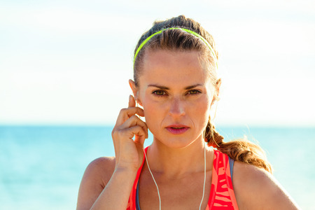 Refreshing wild sea side workout. Portrait of healthy fitness woman in sports gear on the seashore with headphones listening to the music Stock Photo