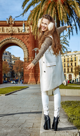 in Barcelona for a perfect winter. Full length portrait of cheerful modern fashion-monger in earmuffs in Barcelona, Spain walking on a parapet