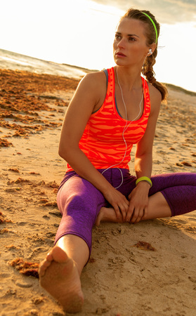 Refreshing wild sea side workout. healthy fitness woman in sport clothes on the seashore looking into the distance sitting at