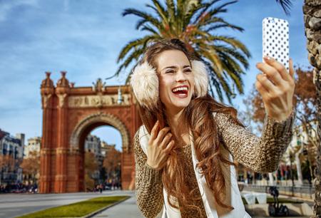 in Barcelona for a perfect winter. Portrait of happy trendy woman in earmuffs near Arc de Triomf in Barcelona, Spain with smartphone taking selfie