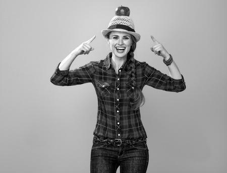あなたのテーブルに健康的な食べ物。頭の上のリンゴを指す黄色に隔離されたチェッカーシャツの幸せな若い女性栽培者の肖像画 写真素材