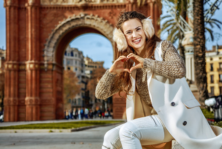 in Barcelona for a perfect winter. Portrait of smiling trendy fashion-monger in earmuffs near Arc de Triomf in Barcelona, Spain showing heart shaped hands