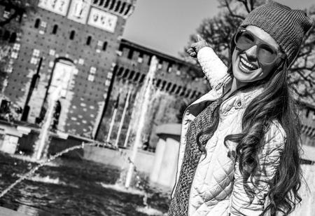 Rediscovering things everybody love in Milan. happy modern traveller woman in Milan, Italy pointing at Sforza Castle Banque d'images - 96848409