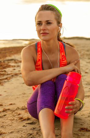 Refreshing wild sea side workout. relaxed fit active woman in sportswear on the beach with water bottle looking into the distance