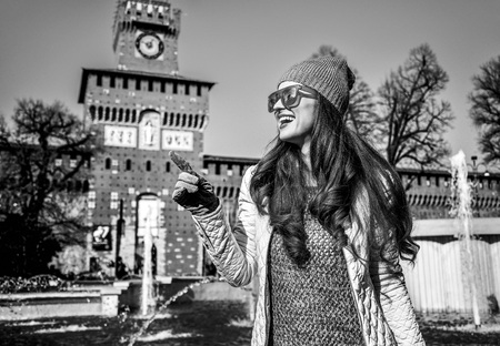 Rediscovering things everybody love in Milan. happy trendy tourist woman near Sforza Castle in Milan, Italy pointing on something Banque d'images - 93321965