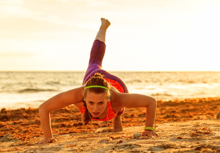 Refreshing wild sea side workout. active fitness woman in sport clothes on the beach doing pushups