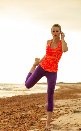 Refreshing wild sea side workout. Full length portrait of active healthy woman in sportswear on the seacoast stretching
